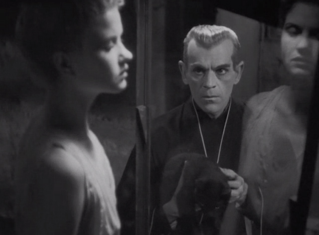 The Black Cat 1934 - Poelzig Boris Karloff looking at another woman in glass while carrying black cat