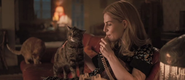 Bohemian Rhapsody - Mary Lucy Boynton petting tabby cat while on phone with other tabby cat on couch behind