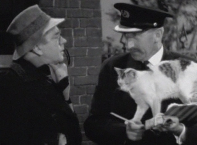 Bulldog Drummond's Secret Police - calico cat standing in station master's arms