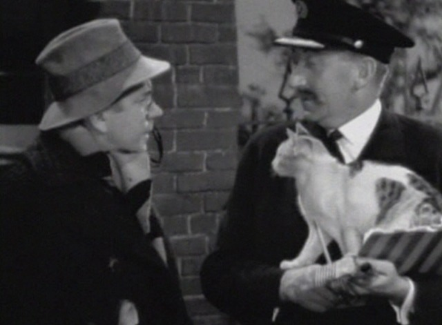 Bulldog Drummond's Secret Police - calico cat sitting in station master's arms