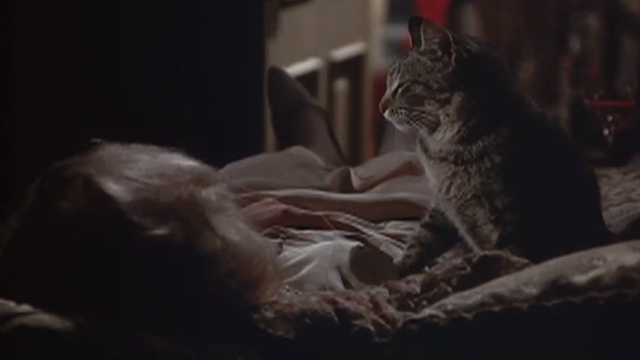Chamber of Horrors - tabby cat sitting next to body of dead woman on bed
