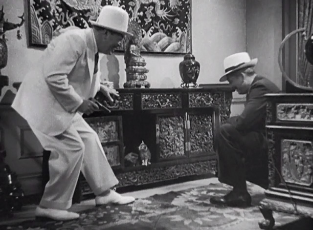 Charlie Chan in Shanghai - Charlie Chan Warner Oland and James Andrew Russell Hicks looking at kittens in cabinet