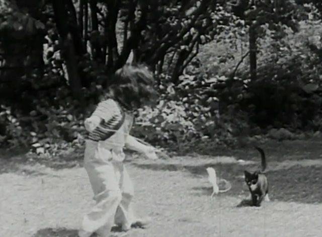A Child Went Forth - tuxedo kitten chasing string pulled by little girl