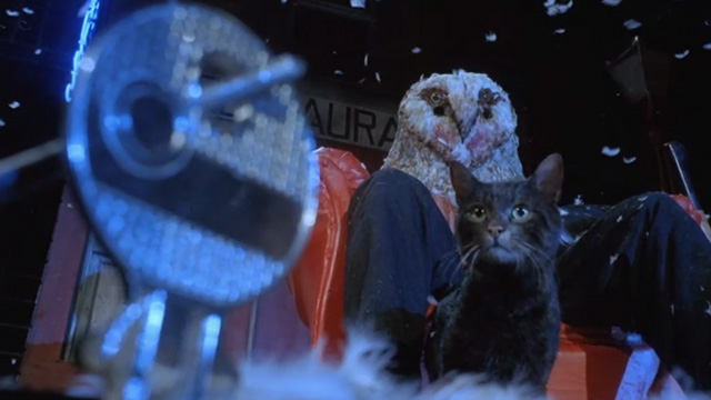 Deliria - close of black tabby cat Lucifer at feet of owl headed killer Wallace on bloody stage with key in foreground