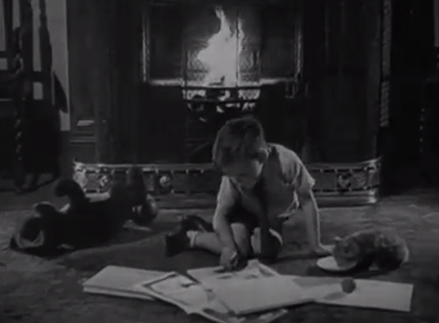 Fire Accidents Trailer - boy with a tabby kitten drinking from a saucer of milk in front of a fireplace