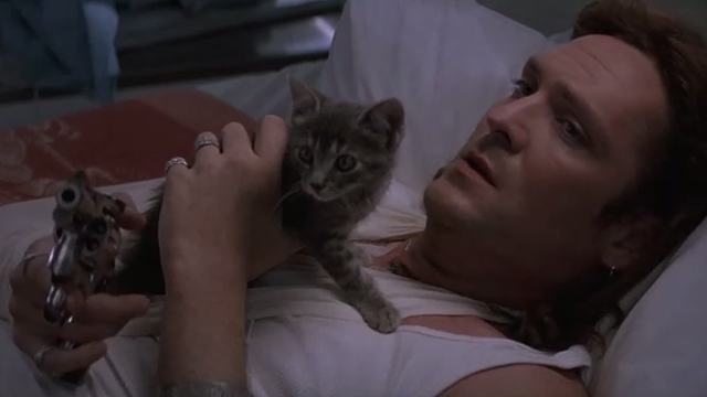 The Getaway - Rudy Michael Madsen lying on table pointing gun with tabby kitten Kitty on chest