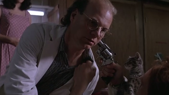 The Getaway - Rudy Michael Madsen lying on table holding gun at Harold James Stephens with tabby kitten Kitty on chest