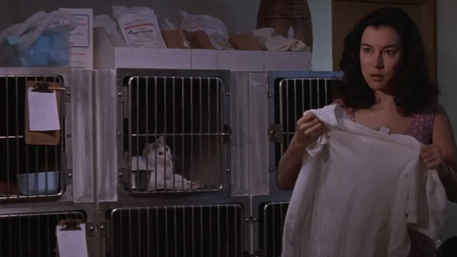 The Getaway - adorable cat in cage in background behind Jennifer Tilly