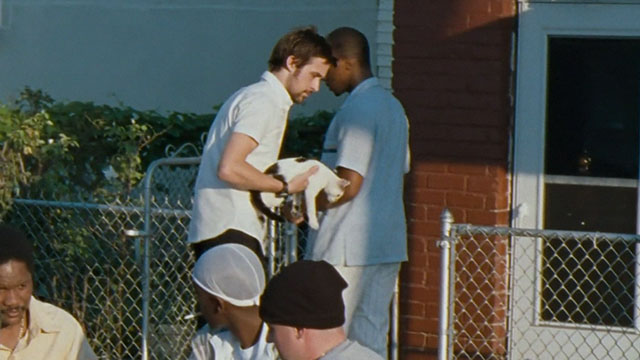 Half Nelson - Dan Dunne Ryan Gosling holding white and black cat with Frank Anthony Mackie