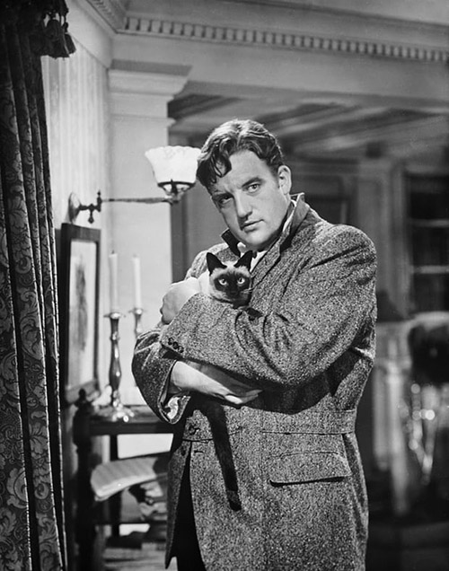 Hangover Square - George Laird Cregar holding Siamese cat publicity still