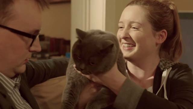 Hell Cat - Charlotte Amy Stephenson holding up gray cat Charlie to Jamie Shane Langan