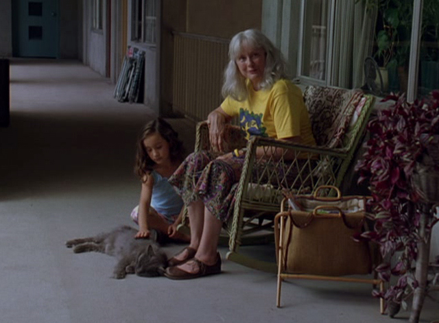 Lady in the Water - Mrs. Bell Mary Beth Hurt and little girl petting long haired gray cat in front of apartment