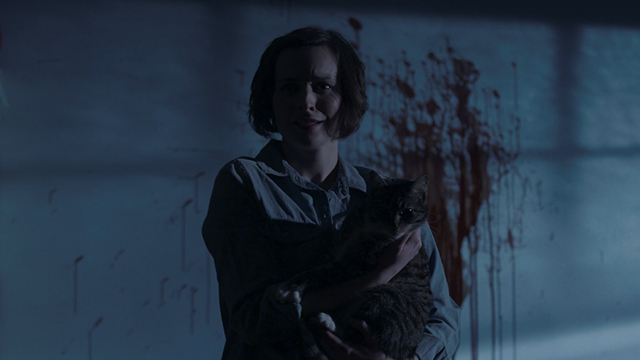 Meow - Samantha Eleonore Dendy holding tabby and white cat with blood on wall