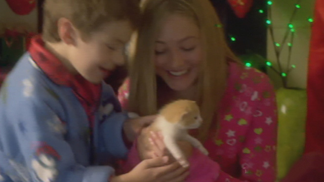 Mistletoe Over Manhattan - Bailey Olivia Scriven and brother Travis Peter DaCunha smiling over tiny orange and white kitten