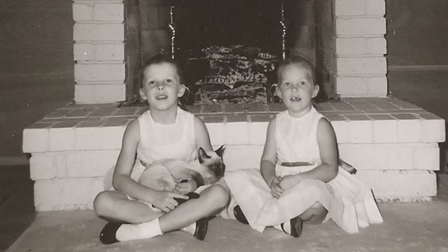 Monogamish - black and white photo of little girls sitting by fireplace with Siamese cat