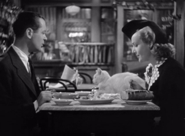 Mr. and Mrs. Smith - David Robert Montgomery looking at white cat on table with Ann Carole Lombard