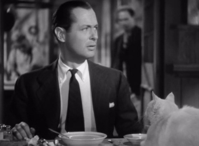 Mr. and Mrs. Smith - David Robert Montgomery looking worried with white cat on table