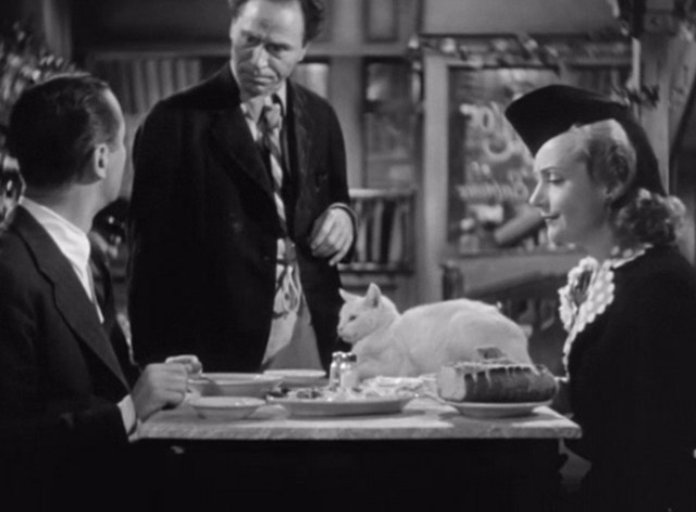 Mr. and Mrs. Smith - Proprietor William Edmunds with David Robert Montgomery and Ann Carole Lombard with white cat on table with