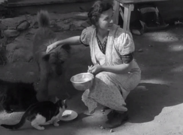 Native Land - farmer's wife Mary George feeding dogs and cat