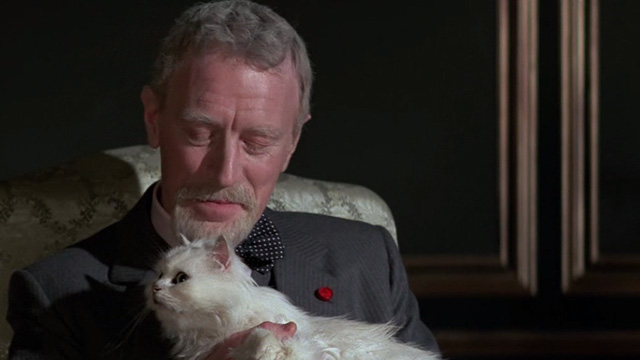 Never Say Never Again - Blofeld Max von Sydow looking down at white Angora cat
