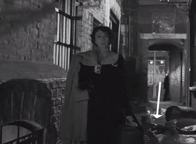 Night and the City - cat drinking water from ground as Helen Googie Withers walks through alley