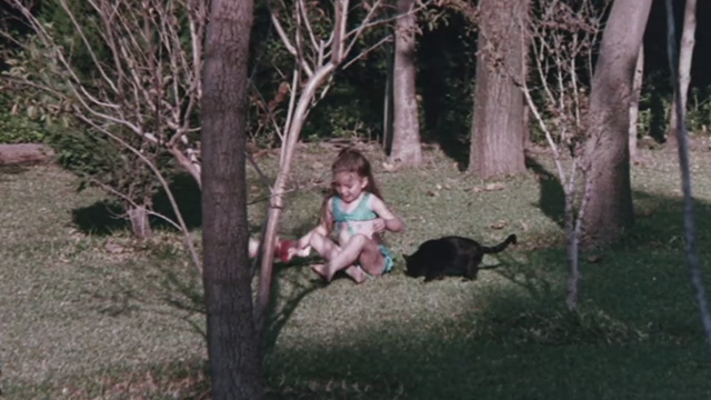 The Night of 1000 Cats - little girl sitting in woods with black cat