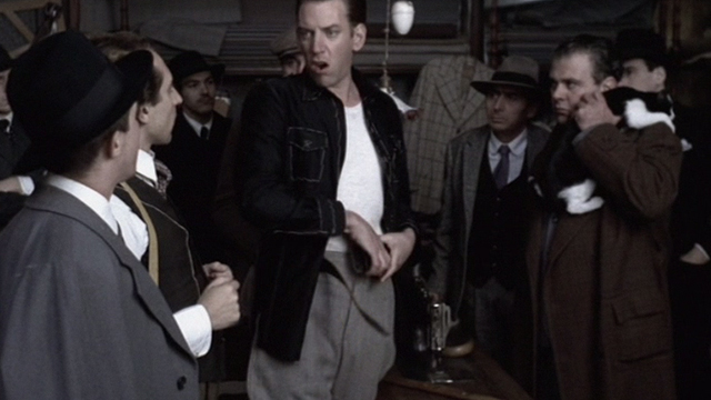Novecento - 1900 - Attila Donald Sutherland taking off belt while man holds tuxedo cat in tailor shop