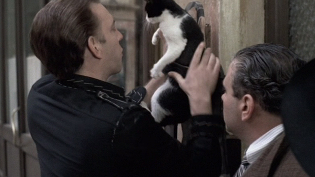 Novecento - 1900 - Attila Donald Sutherland strapping tuxedo cat to tailor shop sign with belt
