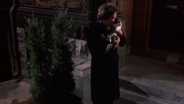 Of Unknown Origin - Bart Peter Weller holding tabby and white cat outside brownstone