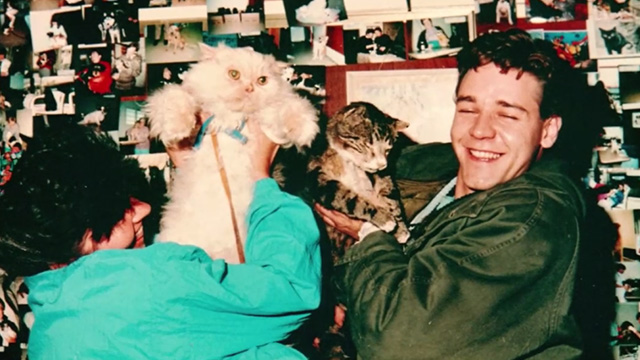 Proof - photo of limp Bengal tabby cat Ugly being held up by Andy Russell Crowe with woman holding cream colored Persian cat