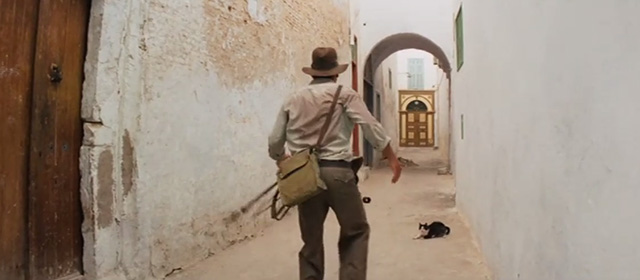 Raiders of the Lost Ark - tuxedo cat in narrow Cairo street as Indiana Jones Harrison Ford turns corner