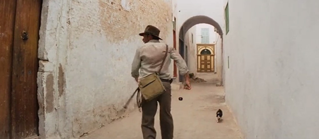 Raiders of the Lost Ark - tuxedo cat moving away in narrow Cairo street as Indiana Jones Harrison Ford turns corner