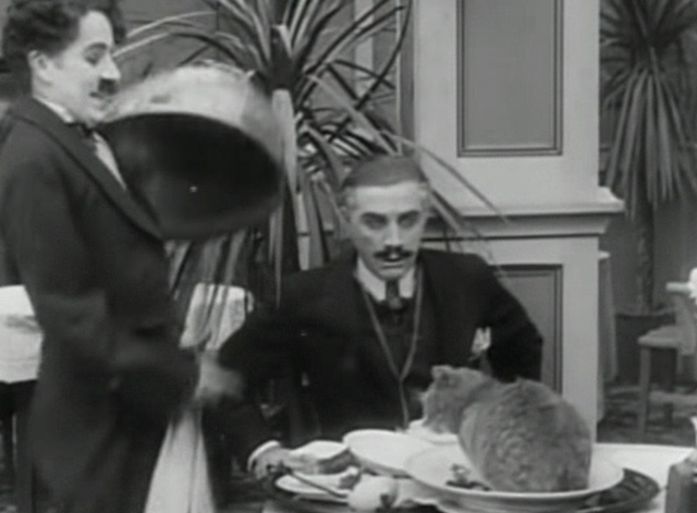 The Rink - waiter Charlie Chaplin uncovering cat on food tray at table