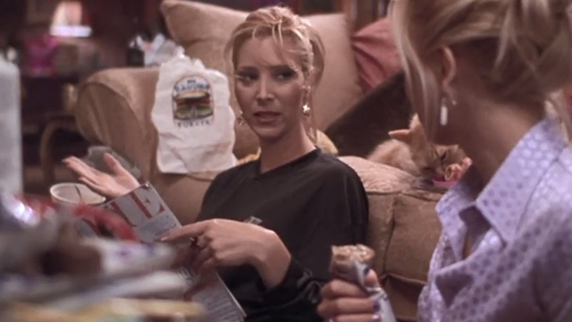 Romy and Michele's High School Reunion - long haired orange tabby cat lying on bed licking ham bone behind Michele Lisa Kudrow and Romy Mira Sorvino