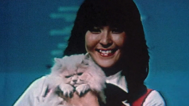Sans Soleil - Japanese woman holding white Angora cat on tv screen