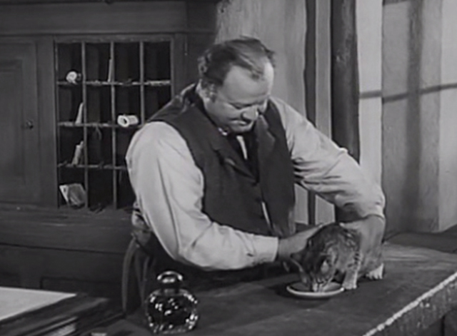 Station West - hotel clerk Burl Ives picking up tabby cat from counter