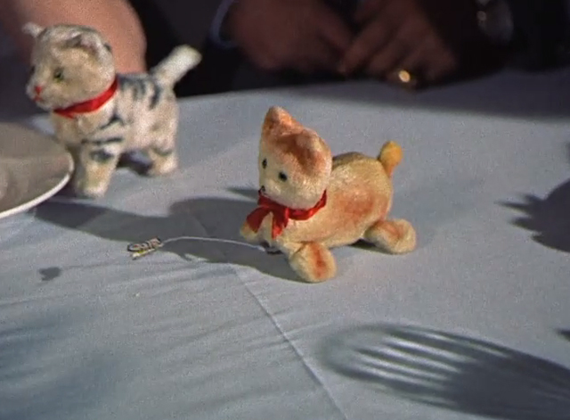 Summertime - cat chasing butterfly wind up toy on table