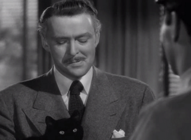 Suspense - over shoulder shot of Frank Leonard Albert Dekker holding black cat