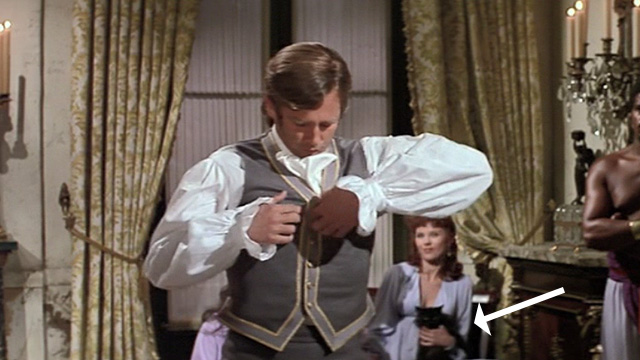 Swashbuckler - long haired black cat held by a woman in background while Major Folly Beau Bridges removes shirt