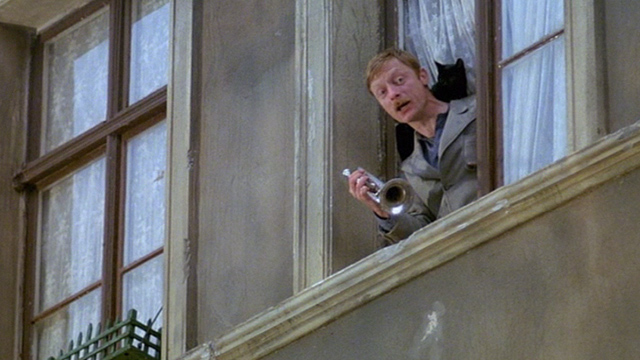 The Tin Drum - Meyn Otto Sander playing trumpet at window with black cat on shoulder