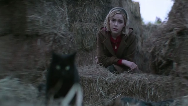 The Chilling Adventures of Sabrina - October Country - black cat Salem with Sabrina Kiernan Shipka in background
