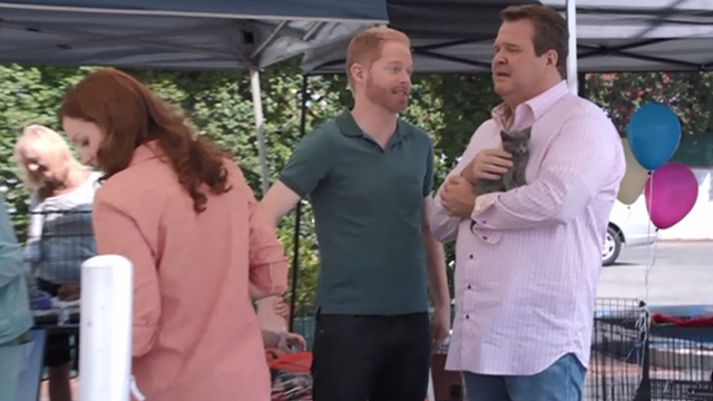 Modern Family - Bringing Up Baby - Mitchell Jesse Tyler Ferguson with Cameron Eric Stonestreet holding gray kitten at adoption fair